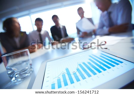 Close-up of business document in touchpad lying on the desk, office workers interacting in the background - stock photo
