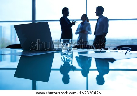 Close-up of business documents, glass of water, eyeglasses and laptop at workplace on background of office workers interacting - stock photo