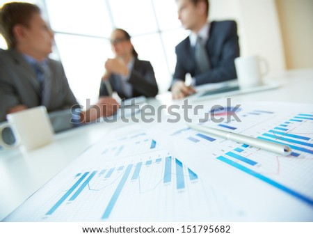 Close-up of business documents lying on the desk, office workers meeting in the background - stock photo
