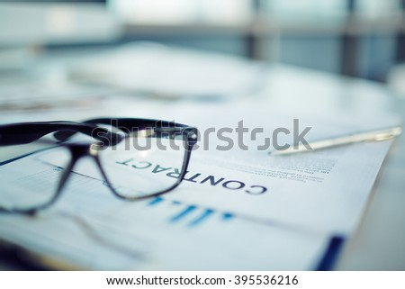 Close-up of business documents with glasses on the table - stock photo