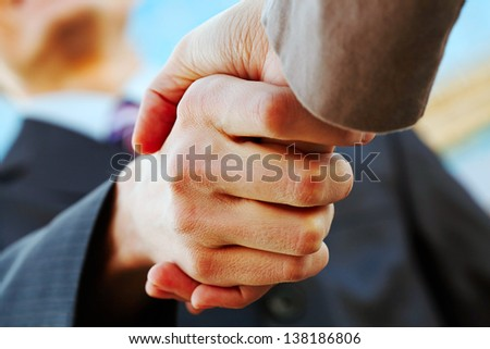 Close-up of business handshake at meeting outdoor - stock photo