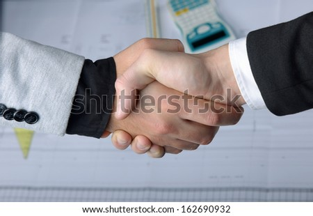 Close-up of business handshake over workplace