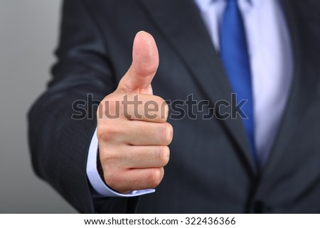 Close up of business man hand with thumb up. Approval positive gesture - stock photo