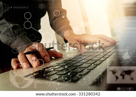 Close up of business man hand working with digital business layers diagram laptop computer on wooden desk as concept - stock photo