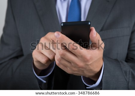 Close up of business man hands reading something on his mobile phone - stock photo