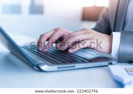 Close up of business man hands typing on laptop computer - stock photo
