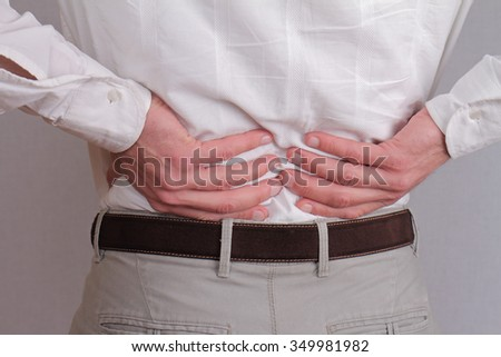 Close up of business man holding his lower back.  Man rubbing his painful back - stock photo