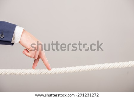 Close-up of business man's hand walking with fingers on rope. Business strategy concept. - stock photo