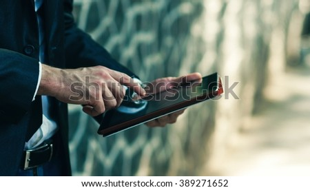 Close up of business man using digital tablet - stock photo