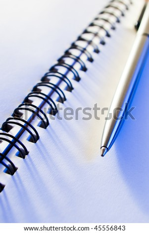 close-up of business note-book with a pen in blue light