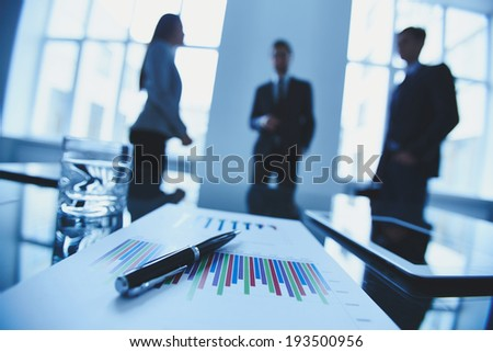 Close-up of business objects at workplace on background of office workers interacting