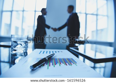Close-up of business objects at workplace on background of partners handshaking - stock photo