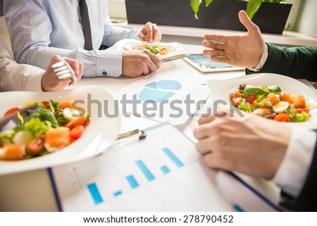 Close-up of business partners discussing the project during business lunch. - stock photo