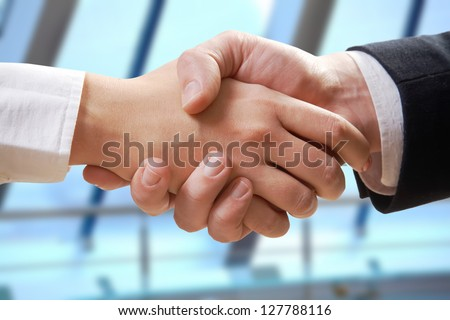 Close- up of business partners making handshake in office - stock photo