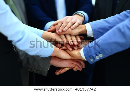 Close-up of business partners making pile of hands at meeting - stock photo