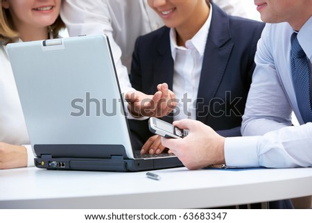 Close-up of business people around laptop working in group - stock photo