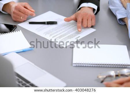 Close up of business people at meeting discussing contract - stock photo