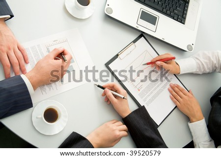 Close-up of business people discussing a financial plan at meeting