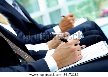 Close-up of business people hands with papers writing at lecture - stock photo