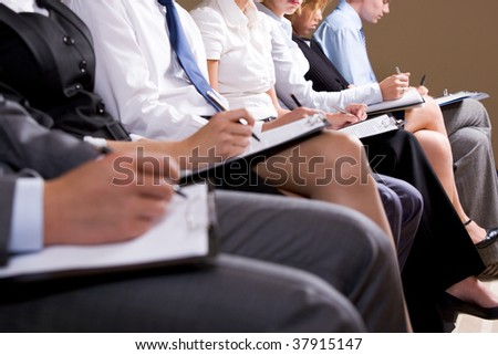 Close-up of business people making notes or writing business plan at conference - stock photo