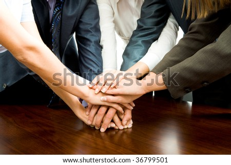Close-up of business people?s hands on top of each other - stock photo