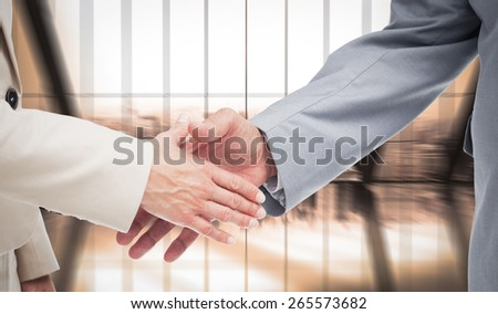 Close up of business people shaking their hands against room with large window looking on city