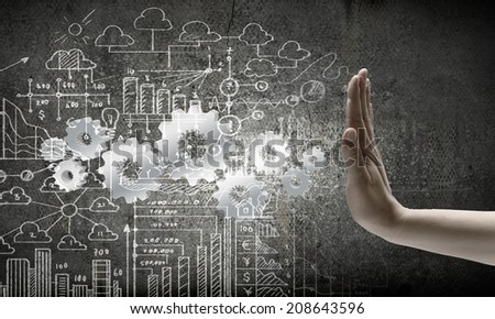 Close up of business person hand and gears - stock photo