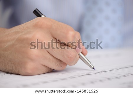 Close-up of business person hand with pen