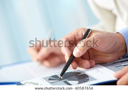 Close-up of business person hand with pen over document - stock photo