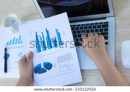 Close-up of business person use laptop with financial diagram