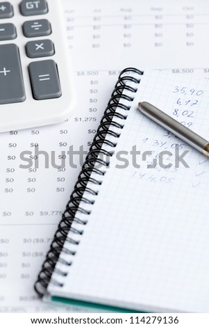 Close up of business stationery: writing pad, pen, calculator and some documents - stock photo