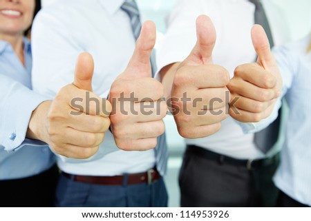 Close-up of business team holding their thumbs up - stock photo