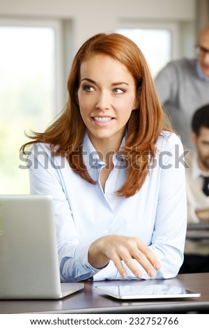 Close-up of business woman working on digital tablet while sitting at meeting.