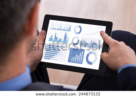 Close-up Of Businessman Analyzing Graph On Digital Tablet - stock photo