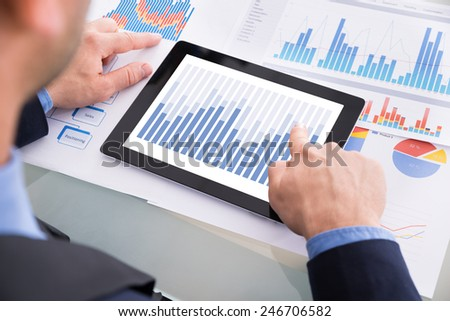 Close-up Of Businessman Analyzing Graph On Digital Tablet Kept Over Documents - stock photo