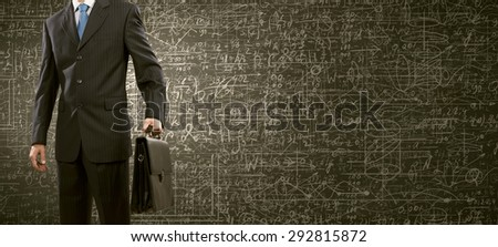 Close up of businessman and business sketch on wall - stock photo