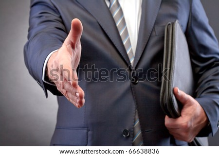 Close-up of businessman arm stretched for handshake - stock photo