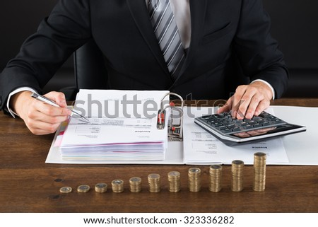Close-up Of Businessman Calculating Invoice With Coins At Desk - stock photo