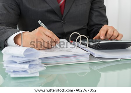 Close-up Of Businessman Calculating Tax At Office Desk - stock photo