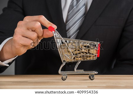 Close-up Of Businessman Carrying Coin In Shopping Trolley At Wooden Desk