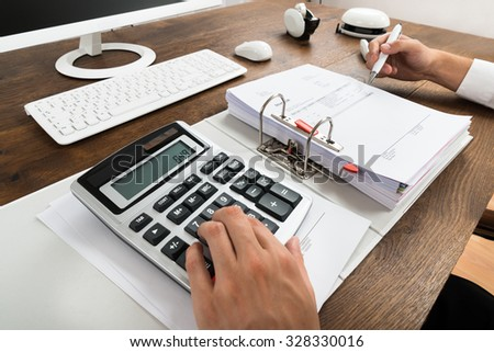 Close-up Of Businessman Checking Invoice With Calculator At Desk - stock photo