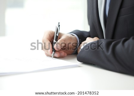 Close-up of businessman fill the form.