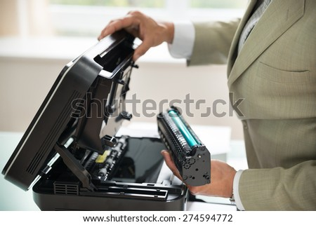 Close-up Of Businessman Fixing Cartridge In Photocopy Machine In Office - stock photo