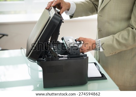 Close-up Of Businessman Fixing Cartridge In Photocopy Machine In Office