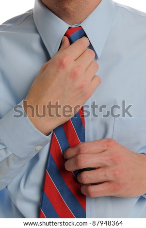Close up of Businessman fixing his tie against a white background - stock photo