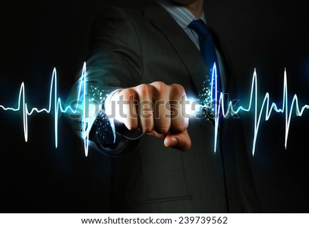 Close up of businessman grasping cardiograph in fist - stock photo