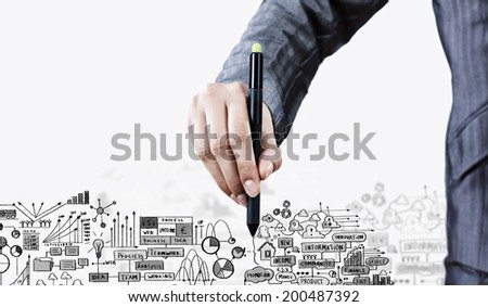 Close up of businessman hand drawing business plan and ideas - stock photo