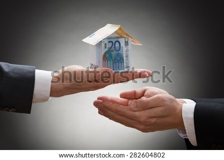 Close-up Of Businessman Hand Giving Money House In Hand Of Businessperson - stock photo