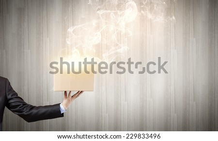 Close up of businessman hand holding carton box - stock photo