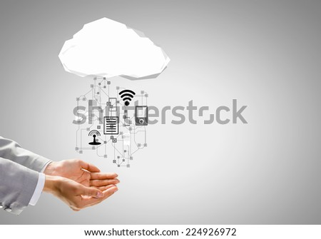 Close up of businessman hand holding cloud with media icons - stock photo